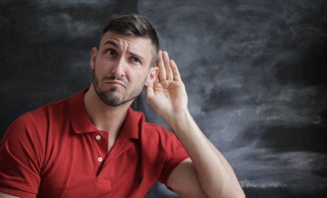 man in red shirt against black background with his hand up to his ear as if listening