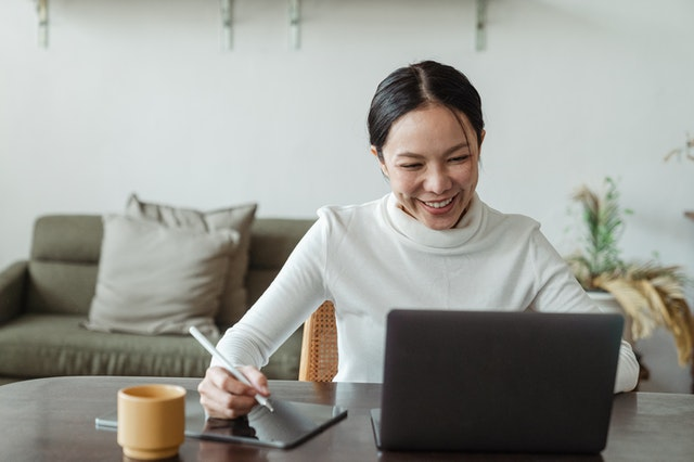 smiling woman writing notes during video call