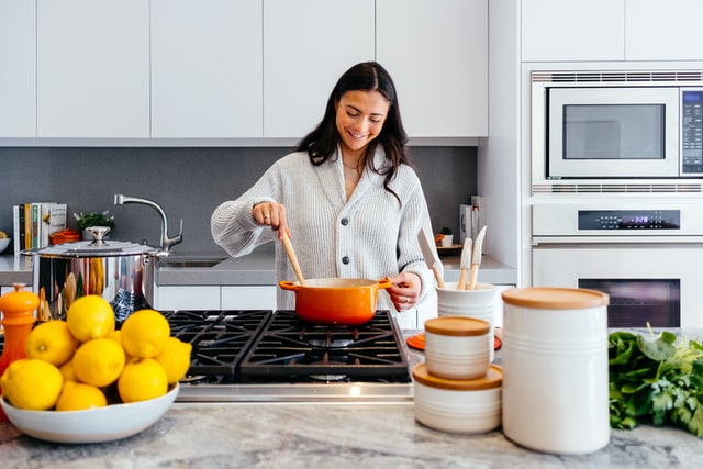 woman cooking and looking down at pot smiling