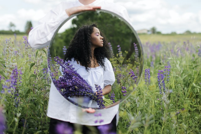 young woman reflected in a mirror someone else is holding. the woman is standing in a lavender field holding a bouquet of lavender