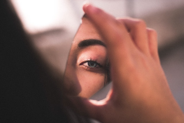 eye on woman reflecting into a shard or mirror she is holding