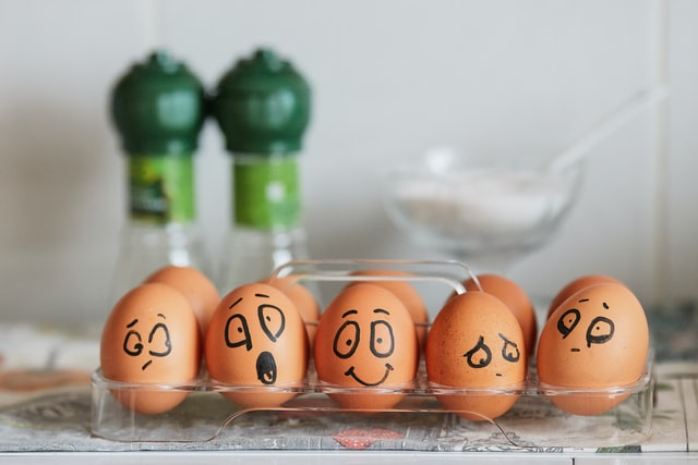 eggs in a carton with faces drawn on them