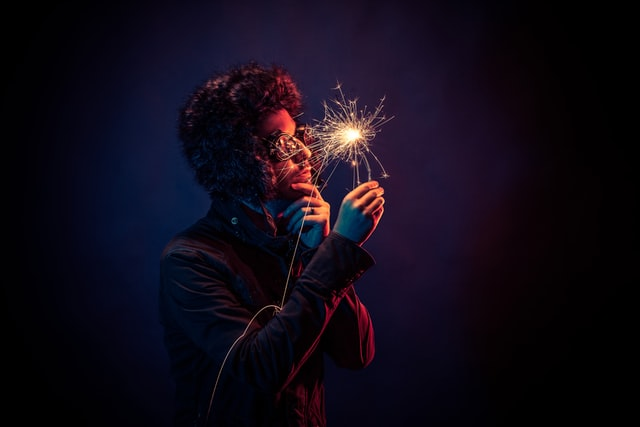 man holding sparkler up to his face pensively