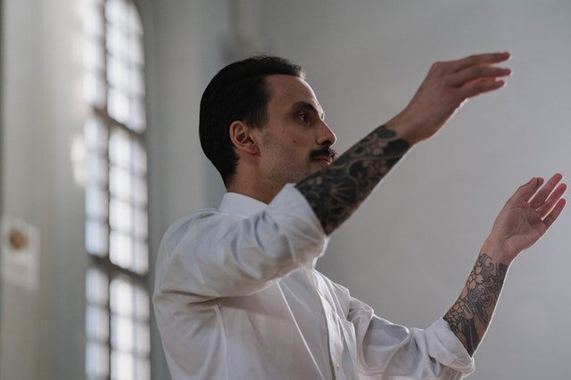 man conducting with his hands. he is wearing a white button down shirt with the sleeves rolled up, revealing tattoo sleeves on both arms