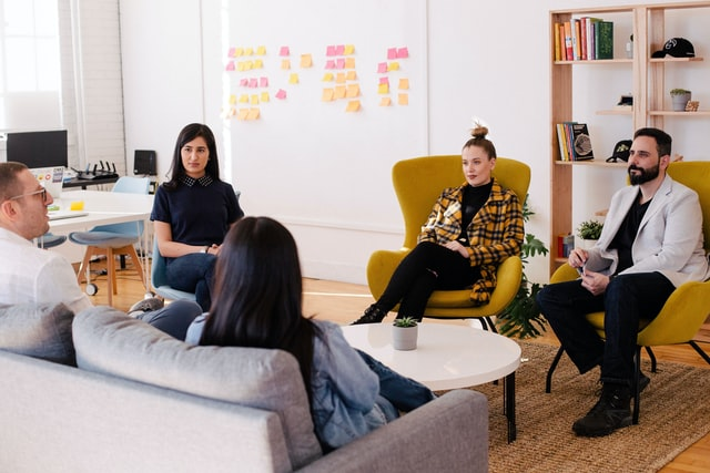 group of people sitting in a circle in an office setting