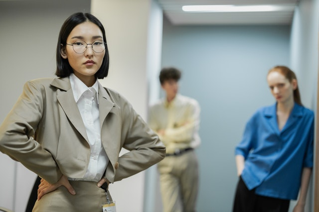 a woman wearing a tan business suit and white button-up in the foreground. she is in focus, hands on her hips and unsmiling. two people are out of focus in the background