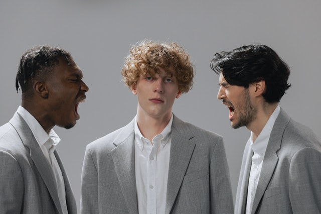 three men, two are yelling at each other while the man in the center stares out of the photo