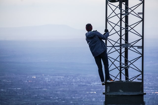 person standing on radio tower overlooking city