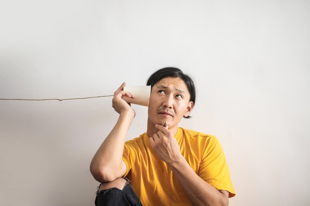 man in yellow shirt with ear to a telephone made of a cup and string