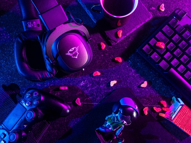 blue and pink lighting over messy gamer's desk, with headphones, control, keyboard, coffee, a spilled box of gummies, and action figures visible