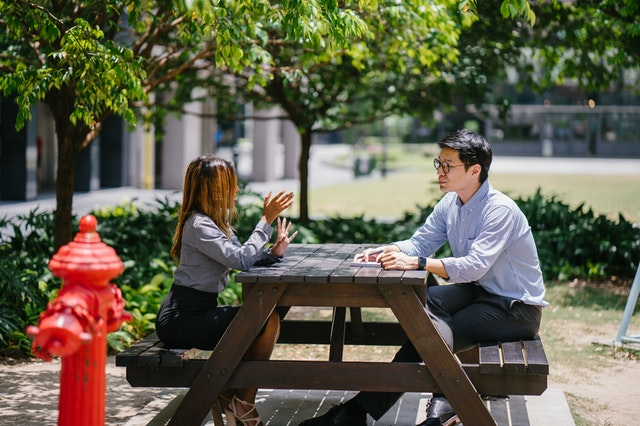 two people sitting at picnic table and talking