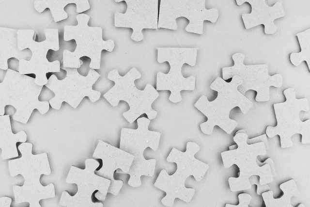 all white puzzle pieces splayed out on a white surface
