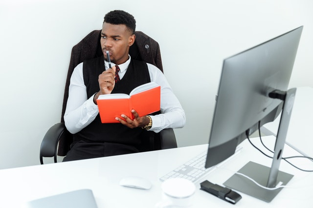 man sitting in chair in front of desktop, holding a notebook open and thinking with pen to lips