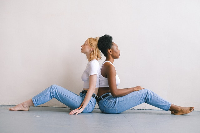 two women sitting back to back on the floor