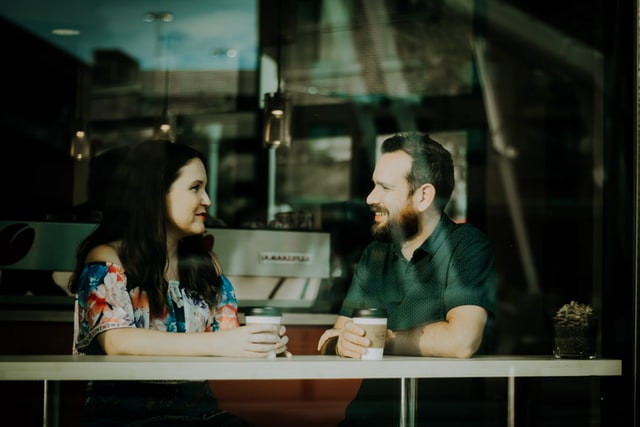 woman and man seated at table and talking, with coffee cups in hand. they are smiling at each other. the image is taken from behind glass