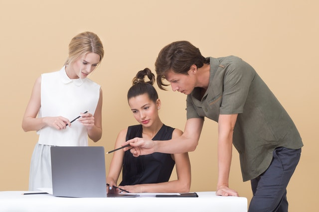 three people gathered around a laptop, one sitting, two standing. one of the people standing is pointing to the screen with a pencil as if making an observation